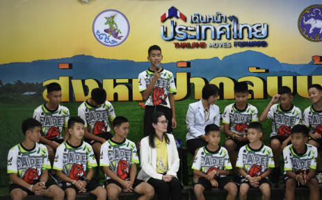 Prachak Sutham (centre), one of the twelve boys dramatically rescued from deep inside a Thai cave after being trapped for more than a fortnight, speaks during a press conference in Chiang Rai on 18 July 2018, following their discharge from hospital. Picture: AFP.
