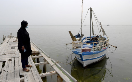 Aminata Traoure, a 28-year-old refugee from Ivory Coast who survived a shipwreck in early March while trying to reach Europe, looks at a boat in the Tunisian coastal city of Sfax, about 270km southeast of the capital, on April 22, 2021. Picture: Fethi Belaid / AFP.