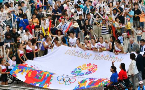 FILE: People gathered at the Tokyo metropolitan government building celebrate and carry a banner after Tokyo won its bid to be the host city of the 2020 Olympics on 8 September 2013. Picture: AFP.