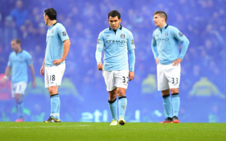 Manchester City's striker Carlos Tevez (C), midfielder Gareth Barry (L) and defender Matija Nastasic (R) react after the English Premier League football match between Manchester City and Manchester United on December 9, 2012. Picture: AFP/Andrew Yates