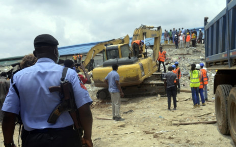 A policeman monitors the excavation of the collapsed guesthouse of the Synagogue Church of All Nations in the Ikotun neighborhood of Lagos on 17 September, 2014. Picture: AFP.