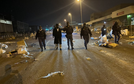 Police Minister Bheki Cele accompanies SAPS officials in Durban as they apprehend looters at warehouses near the N2. Picture: Lirandzu Themba.