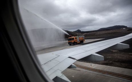 A water truck sprays water to celebrate the first inaugural commercial plane from Johannesburg after it landed at the newly built Saint Helena Airport in the volcanic tropical island of Saint Helena, in the South Atlantic Ocean and part of the British Overseas Territory on October 14, 2017. Picture: AFP.