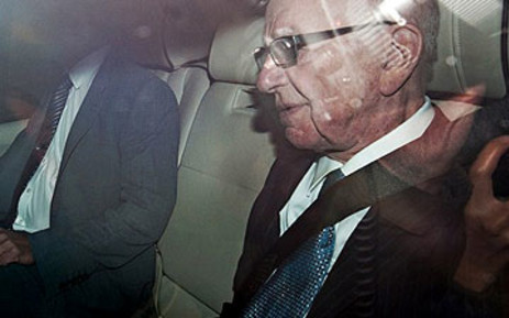 News Corporation Chief Rupert Murdoch (R) leaves his London home in a car with tinted windows on July 19, 2011. Picture: AFP