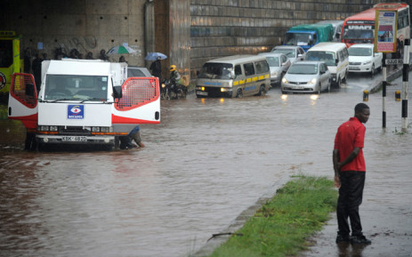 People try to push a truck across a flooded section of road, as a man stands on the side of the road on 29 April, 2016 in the Kenyan capital Nairobi that has been hit by heavy downpours as the long rains season starts. Picture: AFP.