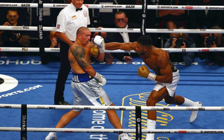 British heavyweight champion boxer Anthony Joshua (R) throws a punch against Ukrainian boxer Oleksandr Usyk during their heavyweight boxing match at Tottenham Hotspur Stadium in north London on September 25, 2021, as Joshua defends his WBA, IBF and WBO heavyweight titles. Picture: Adrian Dennis / AFP