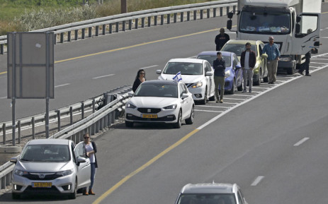 Israelis pause by their vehicles in the main highway leading to Jerusalem on 8 April 2021 as sirens wail across Israel for two minutes marking the annual day of remembrance for the six million Jewish victims of the Nazi genocide. Picture: Ahmad Gharabli/AFP