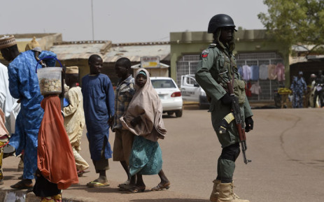 Passers-by walk past a policeman keeping watch at a roundabout in Daura, Katsina State, on 15 February 2019, one day ahead of the presidential and parliamentary elections. Picture: AFP