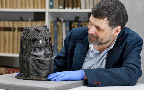 """A handout picture taken on 17 March 2021 at the University of Aberdeen shows Neil Curtis, Head of Museums and Special Collections, posing by a bronze sculpture depicting an """"Oba"""" (king) of Benin acquired by the University at auction in 1957. Picture: Kalyan VEERA/University of Aberdeen/AFP"""