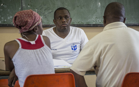 An IEC official helps registered voters clarify their details at the Orlando West high school in Soweto during the voter registration weekend on 5 March 2016. Picture: Reinart Toerien/EWN.
