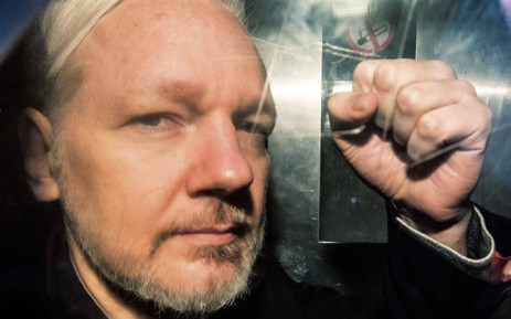 In this file photo taken on 1 May 2019 WikiLeaks founder Julian Assange gestures from the window of a prison van as he is driven into Southwark Crown Court in London, before being sentenced to 50 weeks in prison for breaching his bail conditions in 2012. Picture: AFP