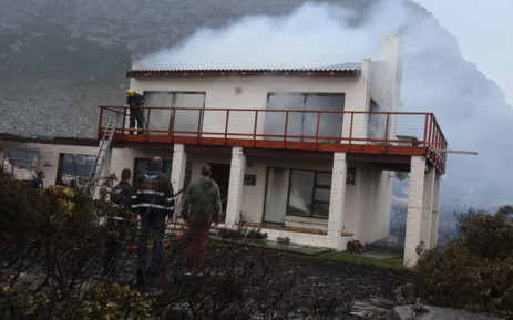 Onlookers watch as a firefighter extinguishes a home that caught alight during a wildfire in the Overstrand region in the Western Cape on 11 January 2019. Picture: EWN