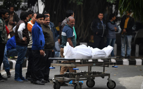 Relatives of an Indian hotel staff member who died in an early morning fire at the property look at his wrapped up body after it was handed over from a mortuary at Lady Hardinge Hospital in New Delhi on 12 February 2019.  Picture: AFP.