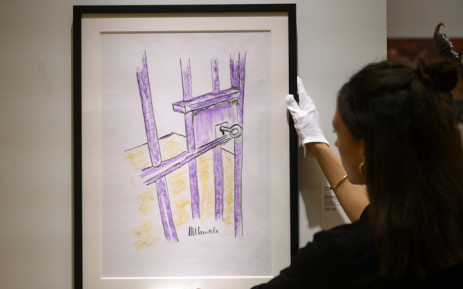 A worker holds a sketch by Nelson Mandela 'The Cell Door, Robben Island' on 26 April, 2019 in New York City. Picture: AFP