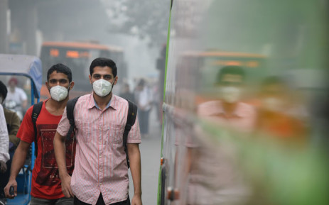 FILE: Indian commuters wear masks as they walk along a road amid heavy smog in New Delhi on 9 November 2017. Picture: AFP