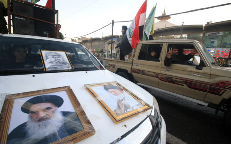 FILE: Members of the Hashed al-Shaabi (Popular Moblisation units) flash the victory gesture as they drive past a pickup truck hanging on its hood portraits of Iraqi Shiite cleric Grand Ayatollah Ali al-Sistani (L) and Iranian supreme leader Ayatollah Ali Khamenei on 10 December 2017. Picture: AFP.