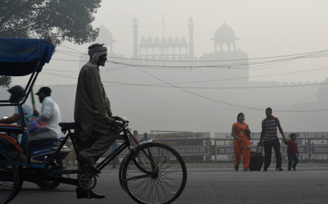 FILE: An Indian family crosses a road amid heavy smog in front of the Red Fort in New Delhi on 10 November 2017. Large swathes of India's northern states remained under dense smog that has shut hundreds of thousands of schools, disrupted air and railway services and forced residents to stay indoors. Picture: AFP.