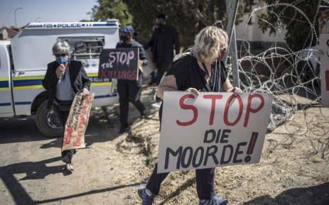 Demonstrators carry placards during a demonstration against farm attacks in Senekal, South Africa, on 16 October 2020, ahead of the appearance of suspects in the Senekal Magistrates Court for the murder case of 22-year-old farm manager Brendin Horner. Picture: AFP