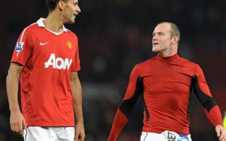 Manchester United's Wayne Rooney (R) leaves the pitch with Rio Ferdinand (L) after their win over Wigan Athletic on 20 November 2010. Picture: Andrew Yates/AFP