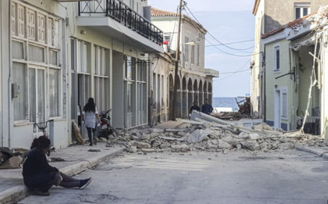 People walk past a destroyed house after an earthquake in the island of Samos, Greece, on 30 October 2020. Picture: AFP.
