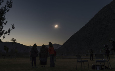 The sun emerges from behind the moon as people watch the total solar eclipse from El Molle, Chile, on 2 July 2019. Picture: APF