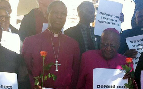 Archbishop Thabo Makgoba and Archbishop Emeritus Desmond Tutu carry a rose for Public Protector Thuli Madonsela which symbolises their support for her and her work. Picture: Chanel September/EWN.