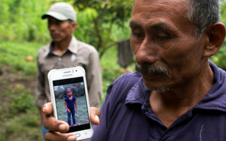 Domingo Caal, 61, grandfather of Jakelin, a 7-year-old girl who died in US custody, holds his mobile phone with a picture of his granddaughter. Picture: AFP.