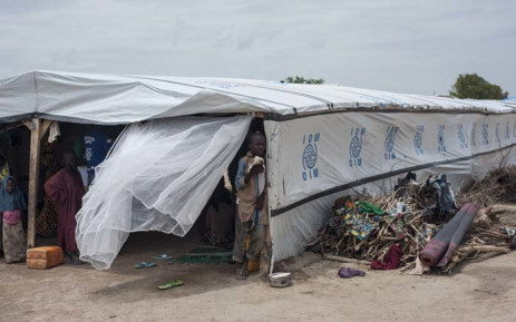 """FILE; Children stand in the shade of a temporary structure in one of the IDP (Internally Displaced People) camps in Pulka on 1 August 2018. As the presidential race heats up ahead of February polls, the Nigerian government and officials of Borno state, the epicentre of the Boko Haram Islamist insurgency, are encouraging and facilitating the """"return"""" of tens of thousands of people. Picture: AFP"""