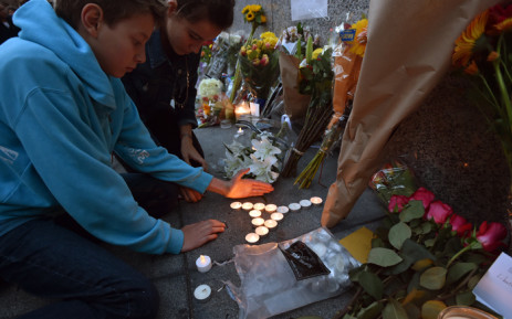 """People place candles in the shape of the Eiffel Tower during a vigil in front of the French Consulate General in San Francisco, California on November 14, 2015, one day after the Paris terrorist attacks. Stirring renditions of """"La Marseillaise"""" rang out from Dublin to New York as global landmarks were bathed in the French colors and thousands marched in solidarity with Paris after attacks that left at least 129 dead. Picture: AFP."""