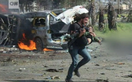 FILE: A screengrab shows Abd Alkader Habak, a photographer and activist, running with a boy in his hands after a bomb attack in Syria. Picture: CNN.