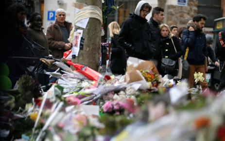 People spend a moment mourning the dead at the site of the attack at the Cafe Belle Equipe on rue de Charonne, prior to going to work early on 16 November 2015 in Paris, three days after the terrorist attacks that left over 130 dead and more than 350 injured. Picture: AFP.