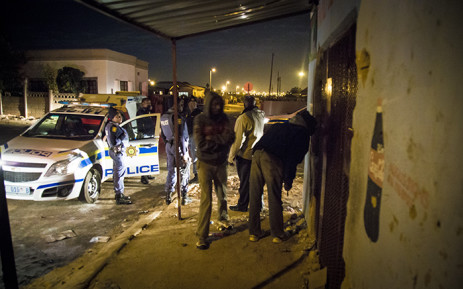 Police and a foreign national inspect his spaza shop in Mamelodi West after it was looted. Picture: Thomas Holder/EWN
