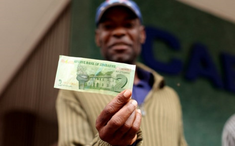 FILE: A man holds a two dollar note that he withdrawn at Cabs Bank in Harare central business centre on 28 November 2016. Picture: AFP