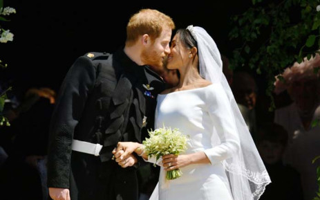 Britain's Prince Harry, Duke of Sussex kisses his wife Meghan, Duchess of Sussex as they leave from the West Door of St George's Chapel, Windsor Castle, in Windsor, on 19 May 2018 after their wedding ceremony. Picture: AFP