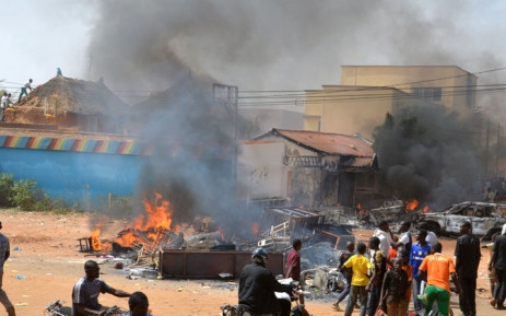 People gather next to rubbles and a hotel set on fire during a demonstration against French weekly 'Charlie Hebdo's' publication of a cartoon of the Prophet Muhammed in Niamey, on January 17, 2015. Picture: AFP.