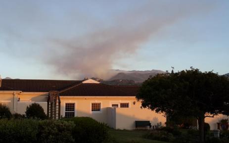 FILE: Fire above Noordhoek towards Silvermine as seen from Fishoek, choppers busy. Picture: Paul van As @Lightningman Twitter.
