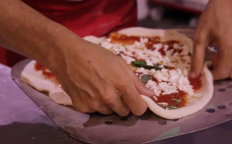 A screengrab of a Neapolitan pizza being prepared.
