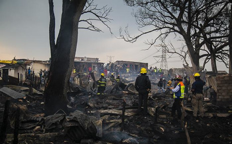 Alexandra resident and firefighters are seen in the area after a City Power electricity pylon and its overhead lines caved in on 5 March 2019, setting fire to multiple shacks. Picture: Kayleen Morgan/EWN
