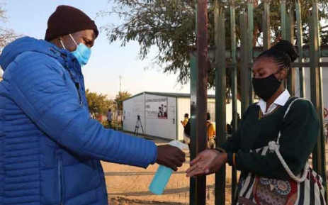 A teacher sanitises the hands of a pupil returning to Olivenhoutbosch Secondary School on 8 June 2020. Picture: Gauteng Provincial Government.