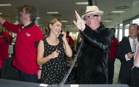 FILE: British radio presenter Chris Evans (right) and British model Kelly Brook (C) are pictured on the trading floor as they attend BGC Partners' Charity Day in London in 2011. Picture: AFP.