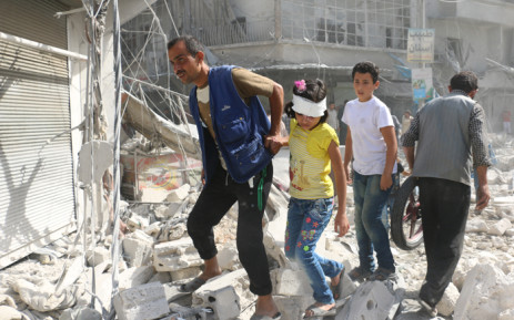 Syrians walk over rubble following air strikes on the rebel-held Fardous neighbourhood of the northern embattled Syrian city of Aleppo on 12 October 2016. Picture: AFP.