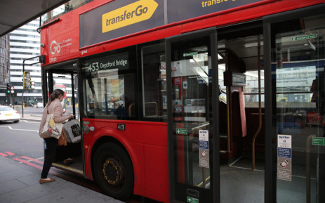 A passenger boards a bus from the front door in central London on April 8, 2020. Picture: AFP.