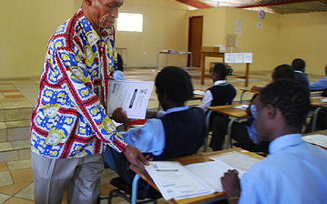FILE: A teacher hands out matric exam question papers at Moletsane High School in Soweto. Picture: EWN