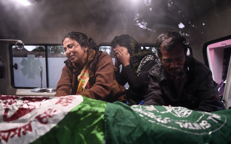 Relatives mourn inside an ambulance next to the dead body of Ishwor Nayak, 25, who was killed after police fired during a protest against the government's Citizenship Amendment Bill (CAB) three days before, in Guwahati on 15 December 2019. Picture: AFP