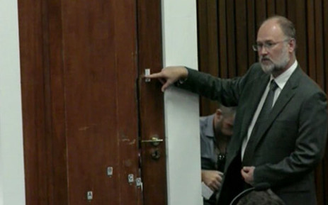 Roger Dixon is pointing out the various cricket bat marks on the door during the Oscar Pistorius murder trial on 15 April 2014.