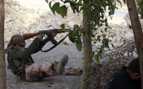 A Syrian rebel fighter shoots sitting on the ground during clashes with pro-regime forces in the northern Syrian city of Aleppo. Picture:  AFP