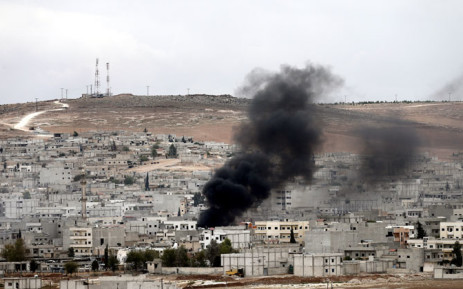 FILE:Smoke rises during armed clashes between Syrian Kurdish fighters and militants from the Islamic State (IS) in and around the town of Kobane, Syria, as seen from the Turkish side of the border.