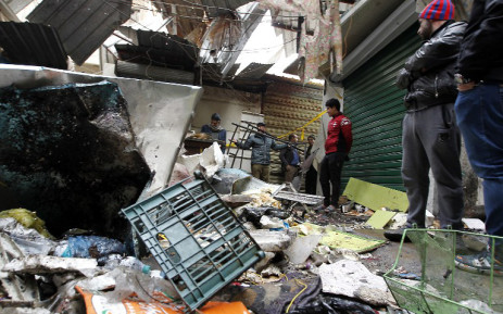 Iraqis look at the aftermath following a double blast in a busy market area in Baghdad's central al-Sinek neighbourhood on December 31, 2016. Baghdad has been on high alert since the start on October 17 of an offensive, Iraq's largest military operation in years, to retake the northern jihadist stronghold of Mosul. SABAH ARAR / AFP