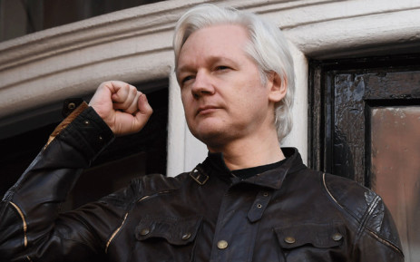 FILE: In this file photo taken on 19 May 2017, Wikileaks founder Julian Assange raises his fist prior to addressing the media on the balcony of the Embassy of Ecuador in London. Picture: AFP.