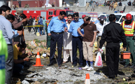 FILE: Pakistani security officials inspect the site of a bomb explosion at a fruit and vegetable market in Islamabad on 9 April 2014. Picture: AFP